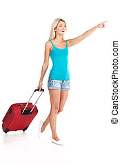 beautiful girl walking with luggage and smiling. young girl pointing on white background