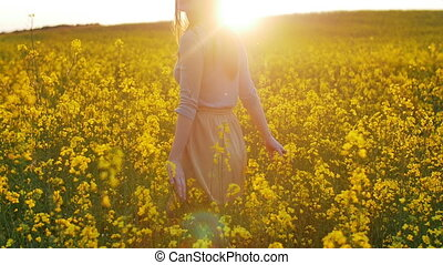 beautiful girl walks on field of flowers at sunset