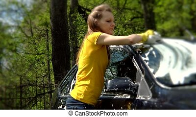Beautiful girl washes her car with sponge. - Beautiful girl...