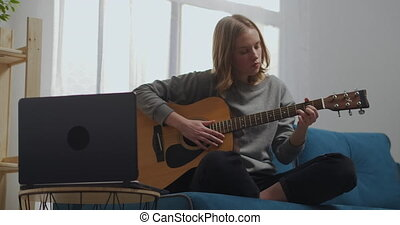 Beautiful girl watching an online lesson isolated. Young woman playing guitar at home. An aspiring musician learns to play a musical instrument using a laptop. High quality 4k footage