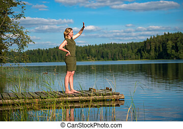 Beautiful girl waving standing on a wooden jetty at a lake