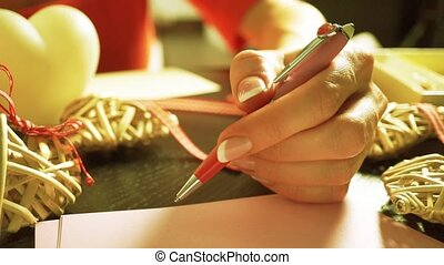 Beautiful girl wearing a red dress hesitating to compose a romantic letter