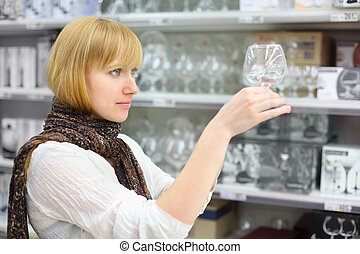 Beautiful girl wearing scarf looks at glass in shop; shallow depth of field