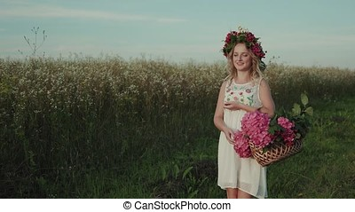 Beautiful girl with a basket of flowers walks in the field