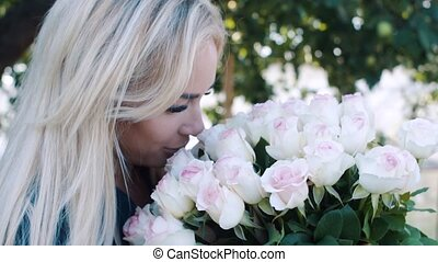 Beautiful girl with a big bouquet of roses in the garden