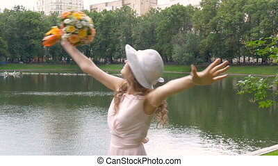 Beautiful girl with a bouquet of flowers whirls in dance. Slow motion