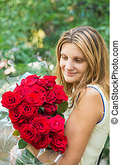 Beautiful girl with a bouquet of red roses