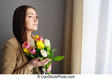 girl with a bouquet of tulips at home