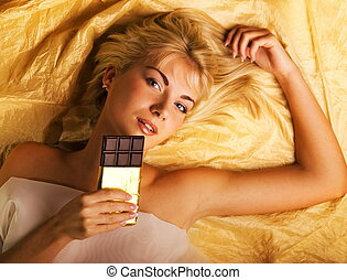 Beautiful girl with a chocolate craving lying on luxury...