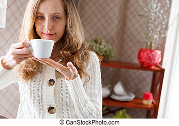 Beautiful girl with a cup of coffee in hand