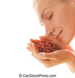Beautiful girl with a handful of strawberries isolated on white background