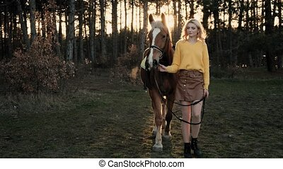 Beautiful girl with a horse walks through the woods at sunset in slow motion