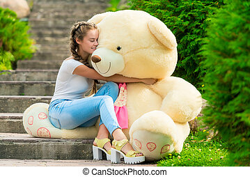 beautiful girl with a huge teddy bear in the park on the stairs