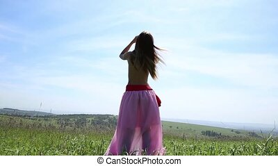 Beautiful girl with a naked torso dancing on a green field, back view