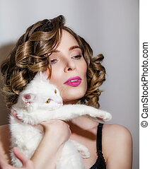 Beautiful girl with a white fluffy cat in her arms.