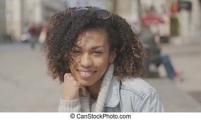 Beautiful girl with afro haircut sitting on bench at city...