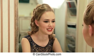 Beautiful girl with amazing makeup and hairstyle in evening dress looks in the mirror and smiles to herself before party