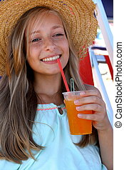 Beautiful girl with an iced drink, straw hat on beach