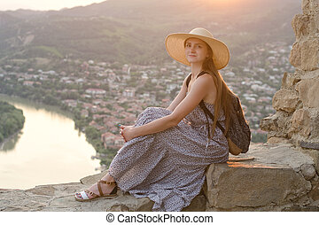 Beautiful girl with backpack in a wide hat sitting on background of the river, mountains and the city below