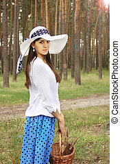 Beautiful girl with basket in the forest