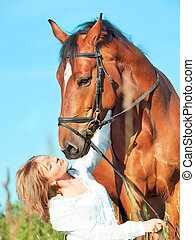 beautiful girl with bay horse at blue sky background