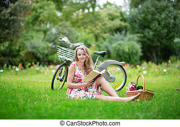 Beautiful girl with bicycle, reading a book