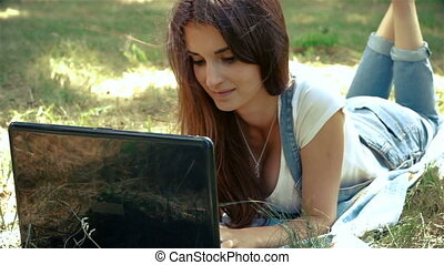 beautiful girl with big black laptop lying on the grass