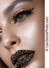 Beautiful girl with black creative art make-up. Beauty face.
