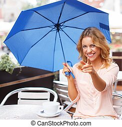 Beautiful girl with blue umbrella sitting in summer cafe