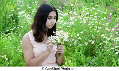 Beautiful girl with bouquet of daisies in a meadow