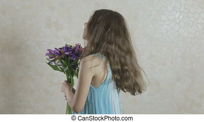 Beautiful girl with bouquet of flowers laughing.