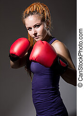 Beautiful girl with boxing gloves, dreadlocks.