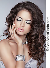 Beautiful girl with brown long wavy hair. Makeup. Jewelry. Attra