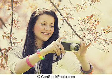 Beautiful girl with camera in spring park