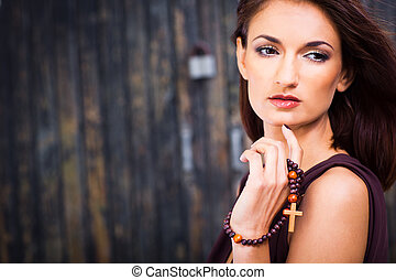 Portrait of beautiful girl in brown dress with christian beads posing against old wooden wall