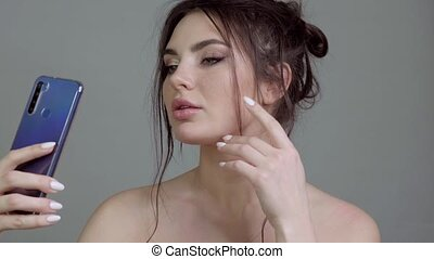 Beautiful girl with classic make-up poses in front of the phone camera.