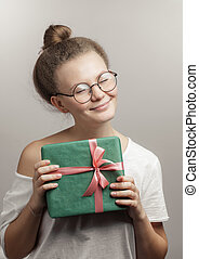Beautiful girl with closed eyes is holding a gift box isolated