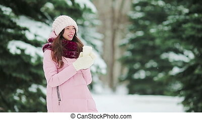 Beautiful girl with coffee to go outdoors on beautiful winter snow day