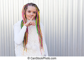 Beautiful girl with colored dreadlocks summer sunny day in a white jacket and lips finger asking for silence