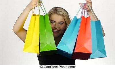 Beautiful girl with colorful packages. Shopping. White. Slow motion