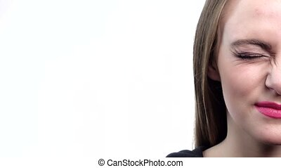 Beautiful girl with crimson lipstick winking, half-face, closeup