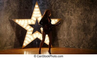 beautiful girl with electric guitar, shining star in the background. slow motion, silhouette