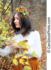 Beautiful girl with flower wreath among branches of autumn outdoors