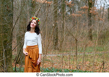 Beautiful girl with flower wreath on her head in the autumn forest