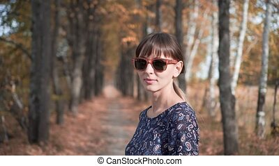 Beautiful girl with glasses smiling in a forest