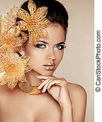 Beautiful Girl With Golden Flowers. Beauty Model Woman Face...