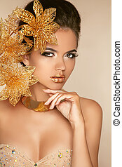 Beautiful Girl With Golden Flowers. Beauty Model Woman Face. Perfect Skin. Professional Make-up. Makeup. Fashion Art Photo.