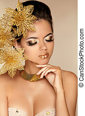 Beautiful Girl With Golden Flowers. Beauty Model Woman Face. Perfect Skin. Professional Make-up. Makeup. Fashion Art