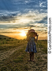 Beautiful girl with hat at the sunset