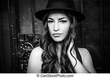 beautiful girl with hat portrait in the city black and white